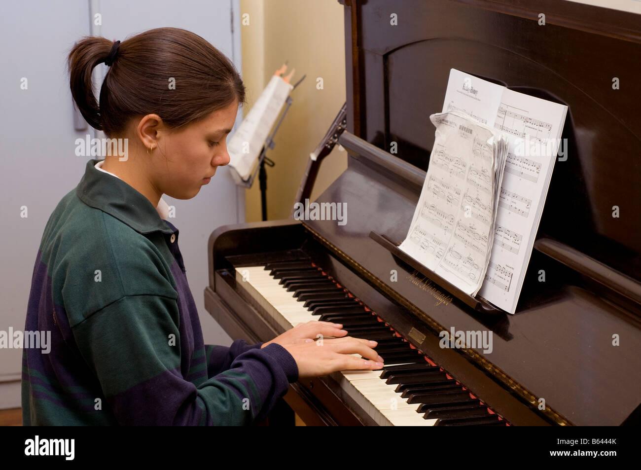 Schoolgirl practicing piano - Stock Image