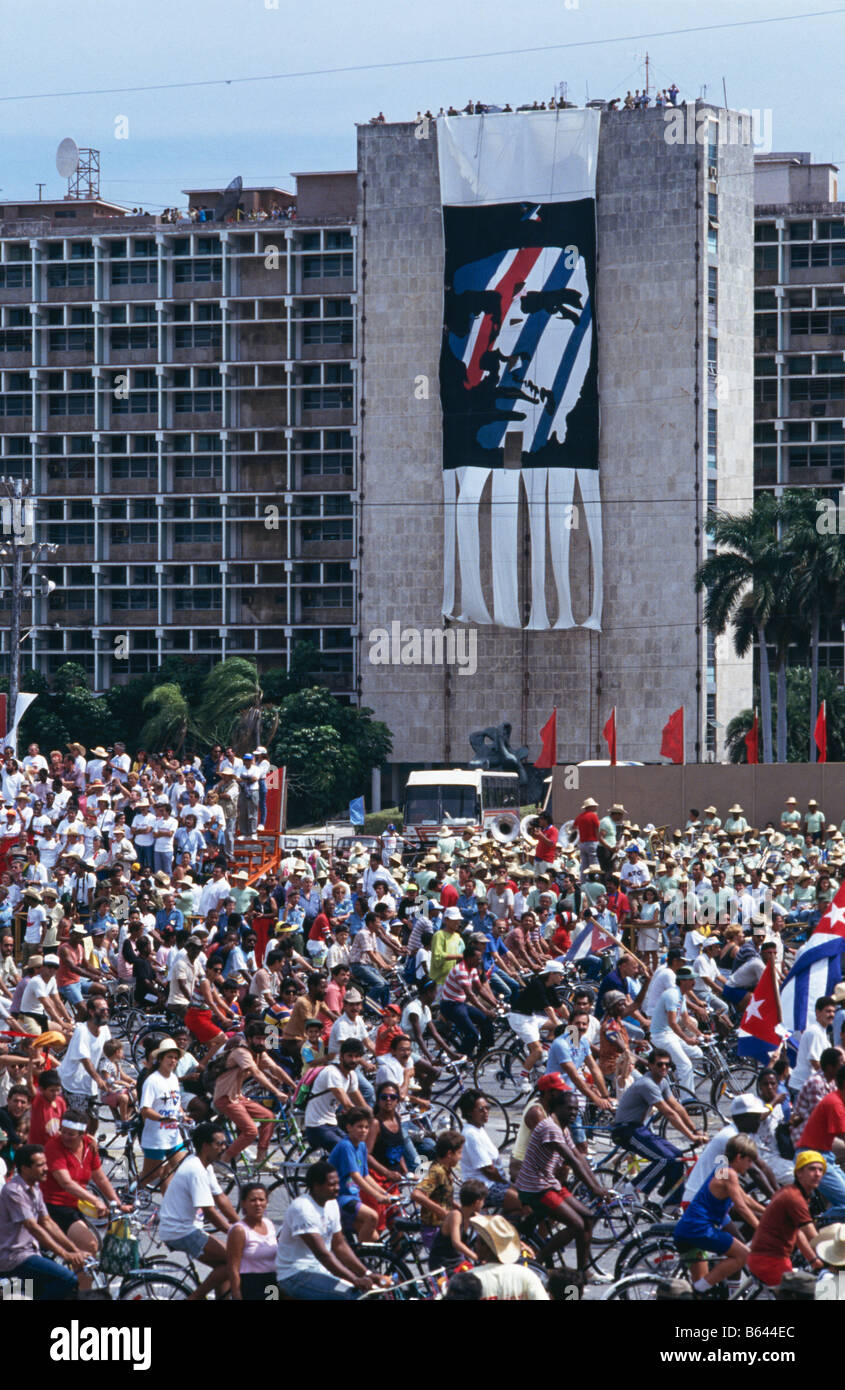 Supporters of government during May Day celebrations cycling past a portrait of Che Guevara, in Havana, Cuba, 1993 - Stock Image