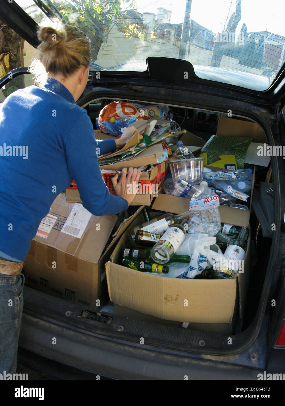 Woman filling car trunk with recyclable rubish - Stock Image