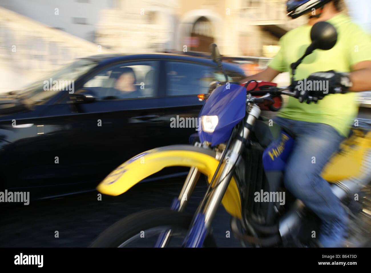 man riding husqvarna motorbike in street in city town - Stock Image