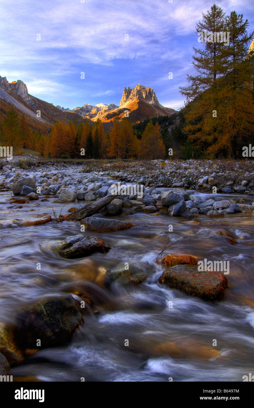 An autumnal view of the Valle Stretta in Italian Alps. the Grand Seru peak, the Dora river and fall colours - Stock Image