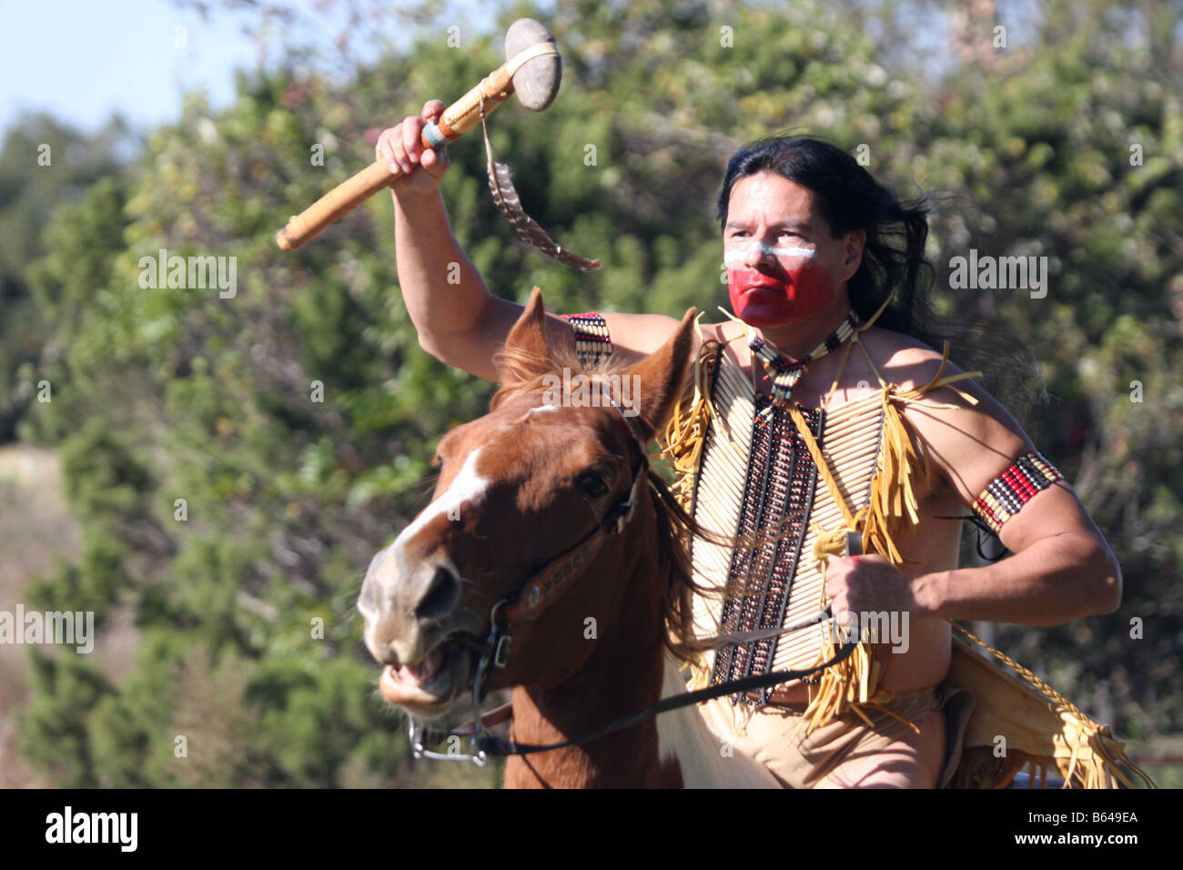 An Apache Native American Indian running horseback waving a stone hammer in attack - Stock Image