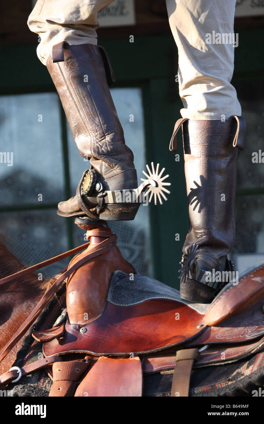 A cowboy standing on top of his saddle on his horse Stock Photo
