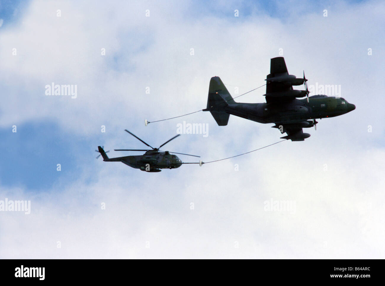 US Air Force KC 130 refueling tanker refuels Jolly Green Giant helicopter, in flight - Stock Image