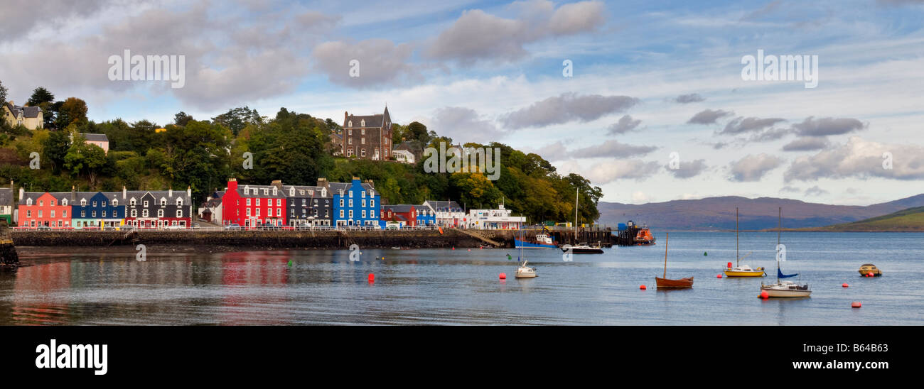 Panoramic photo of sea front and harbourside of Tobermory, Isle of Mull, Scotland taken on a bright but cloudy day - Stock Image