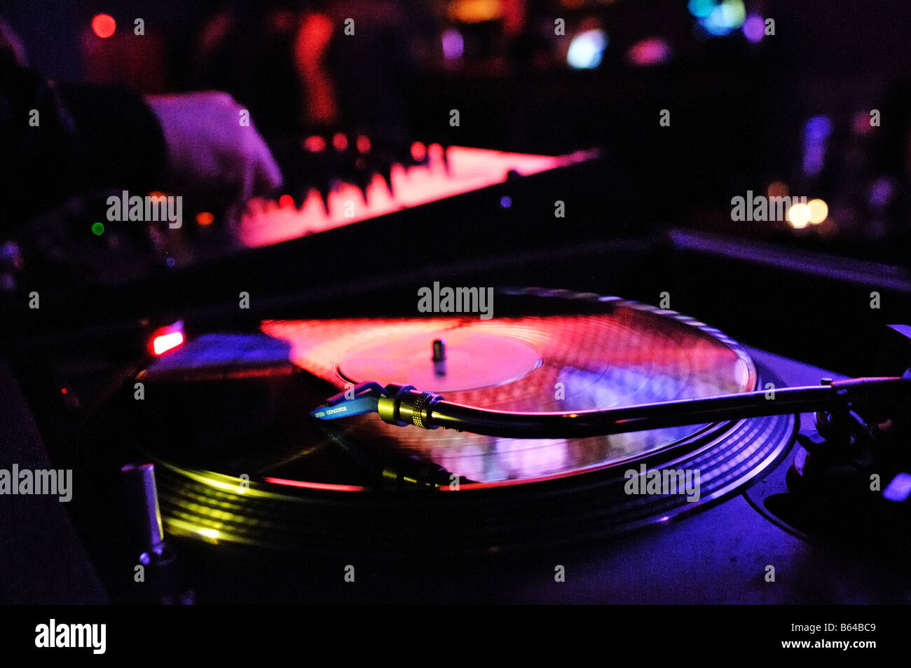 Record playing on a deck with a DJ Stock Photo