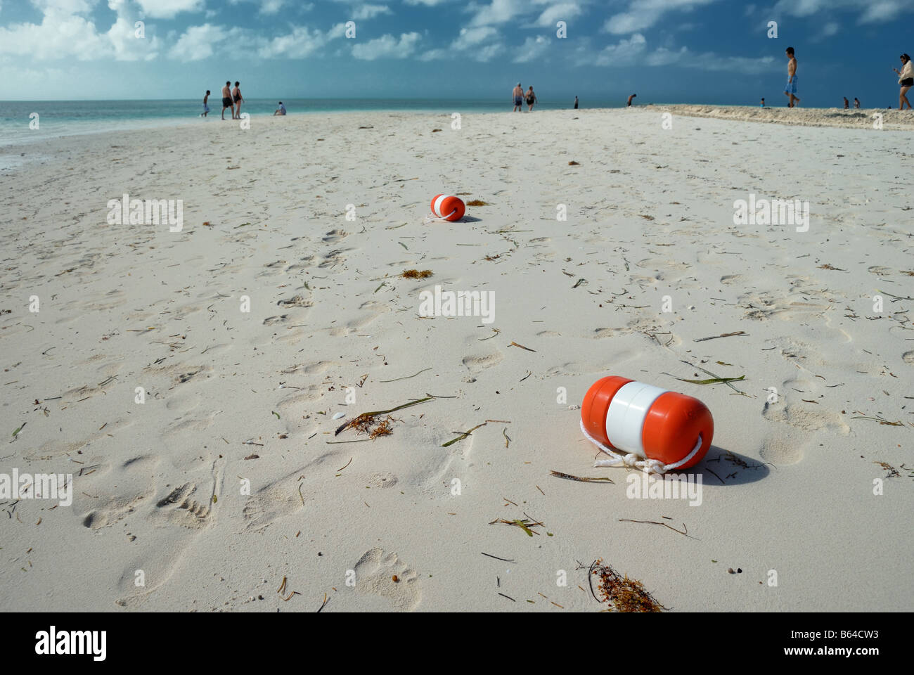 Bouys washed up on the sandy beach at Little Stirrup Cay, Bahamas, with people in the distance. - Stock Image
