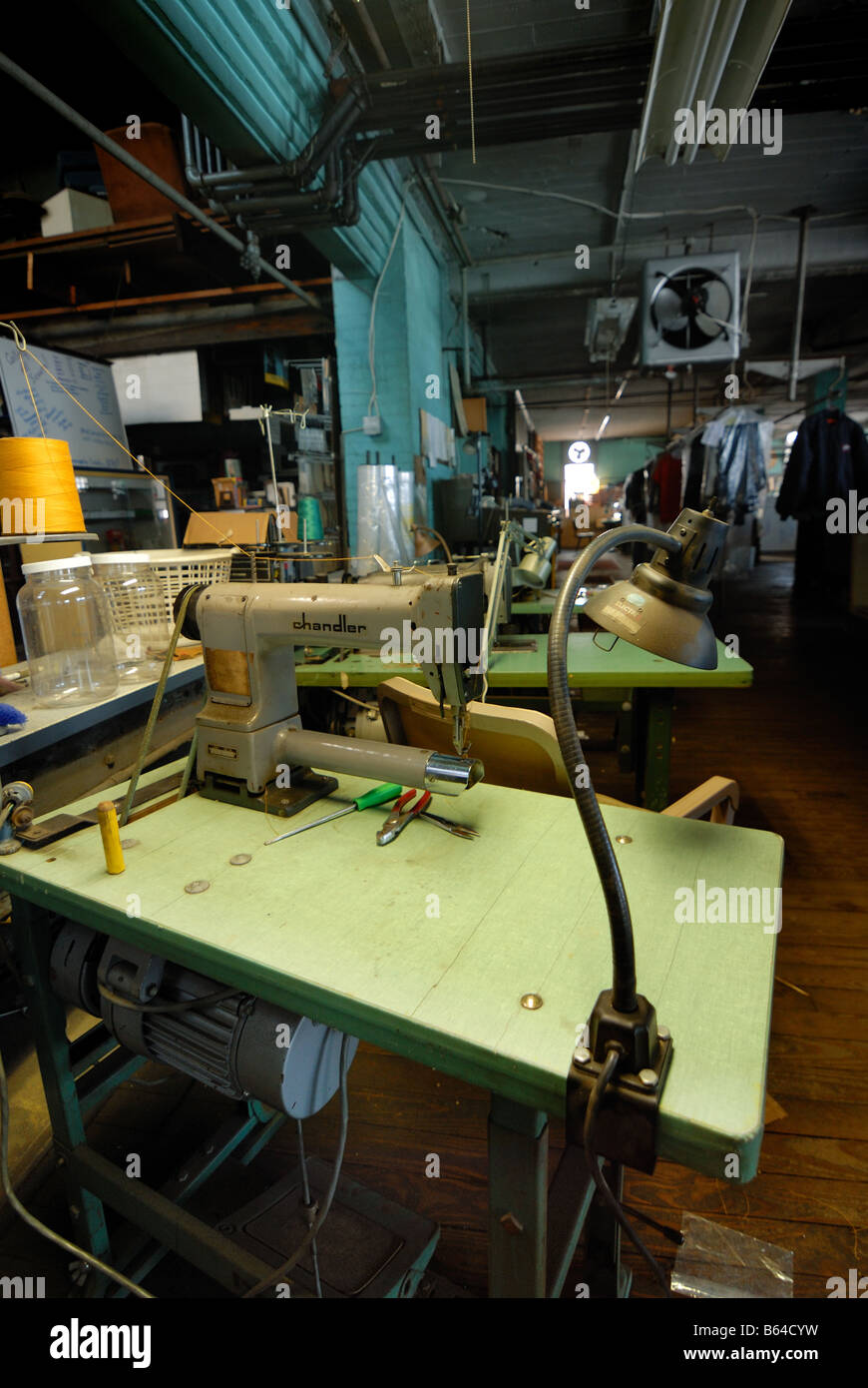 One of many old sewing machines and workspaces for seamstresses or tailors in a dry cleaning and alternations shop - Stock Image