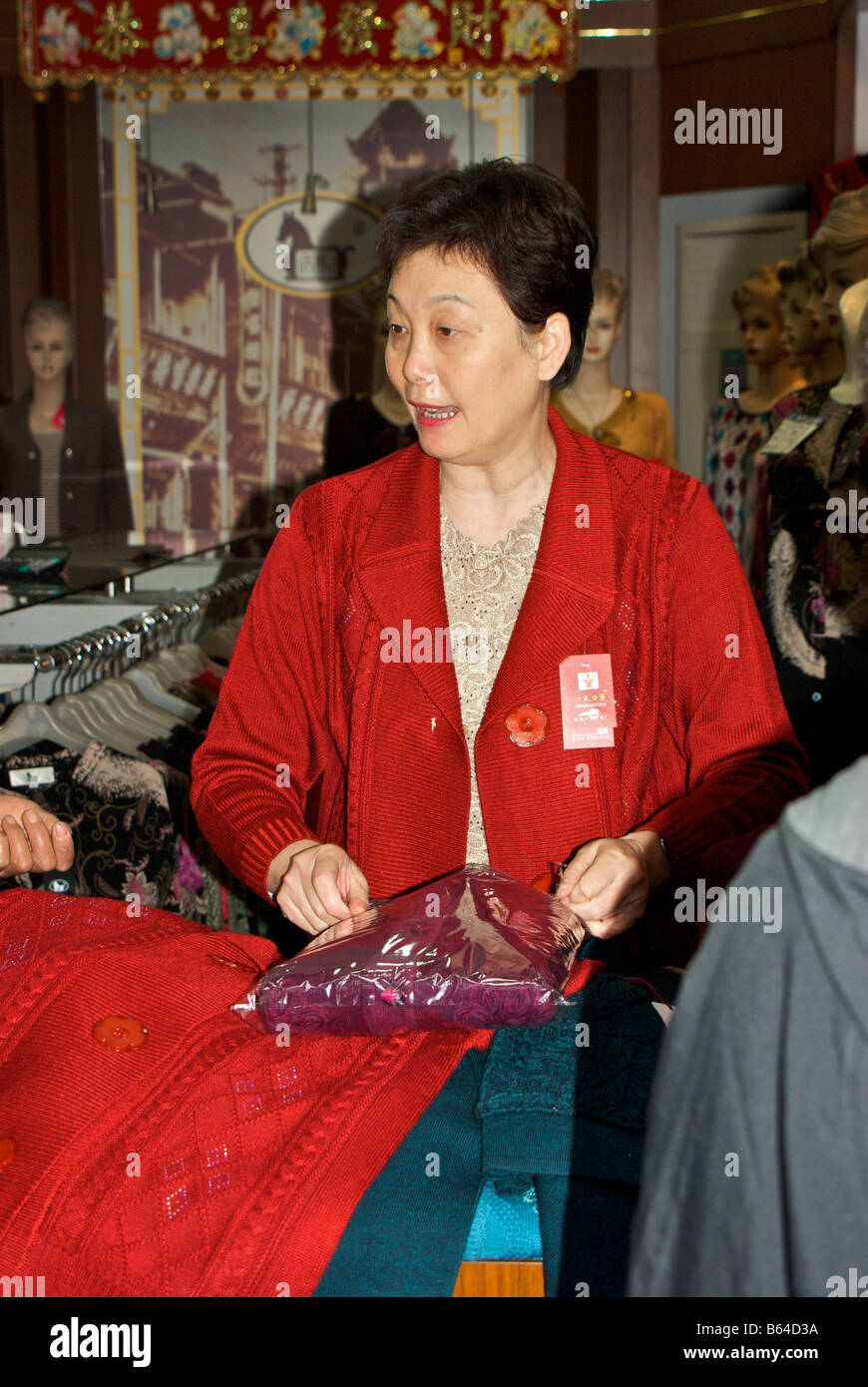 Woman proprietor packaging knitted wear for a customer in her small clothing shop stall in City God Temple Shanghai - Stock Image