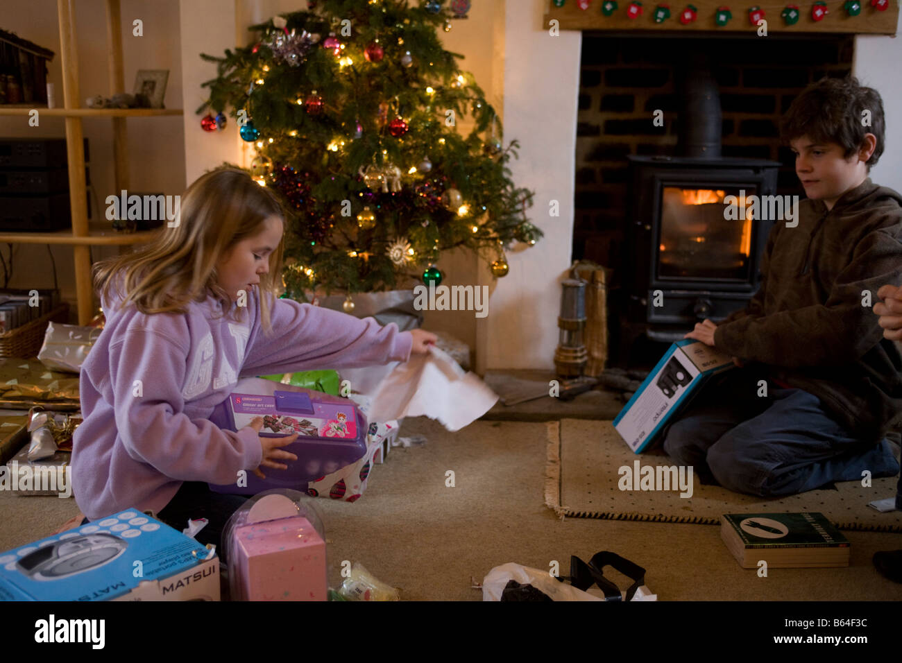 7 year old girl opening a Christmas present in front of her brother ...
