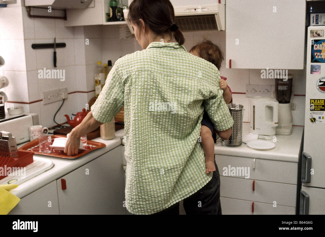 mother preparing meal while copying with a baby Stock Photo