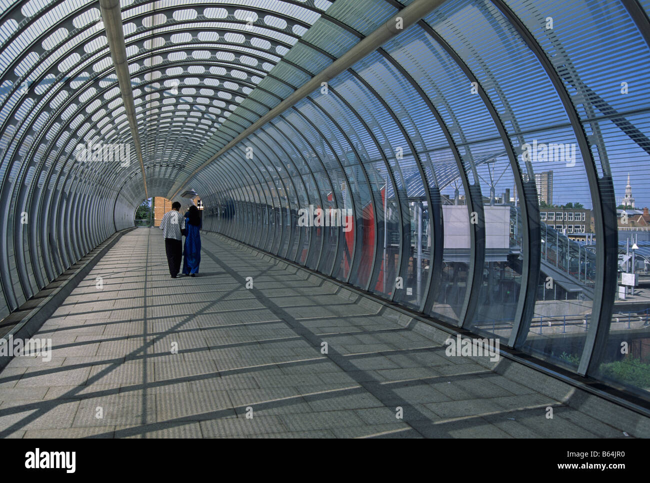 Asian couple in the footbridge tunnel of Poplar DLR station London docklands England - Stock Image