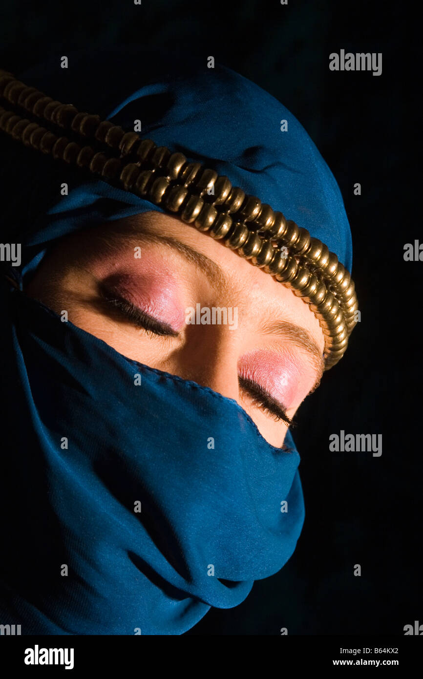 Young woman with decorative headress and yashmak type veil covering her face - Stock Image