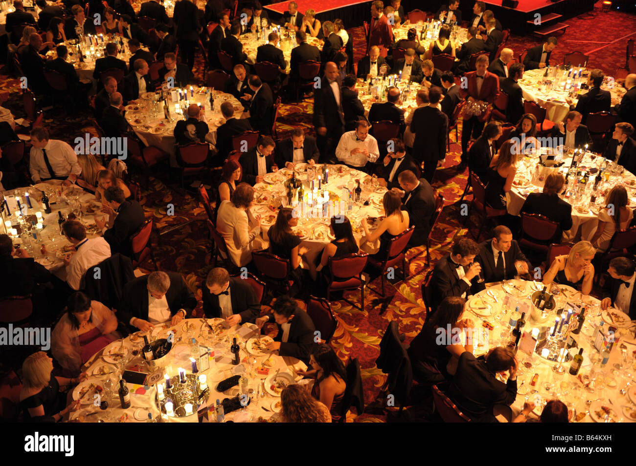 Large evening dinner function with many tables of people. Elevated aerial view. - Stock Image