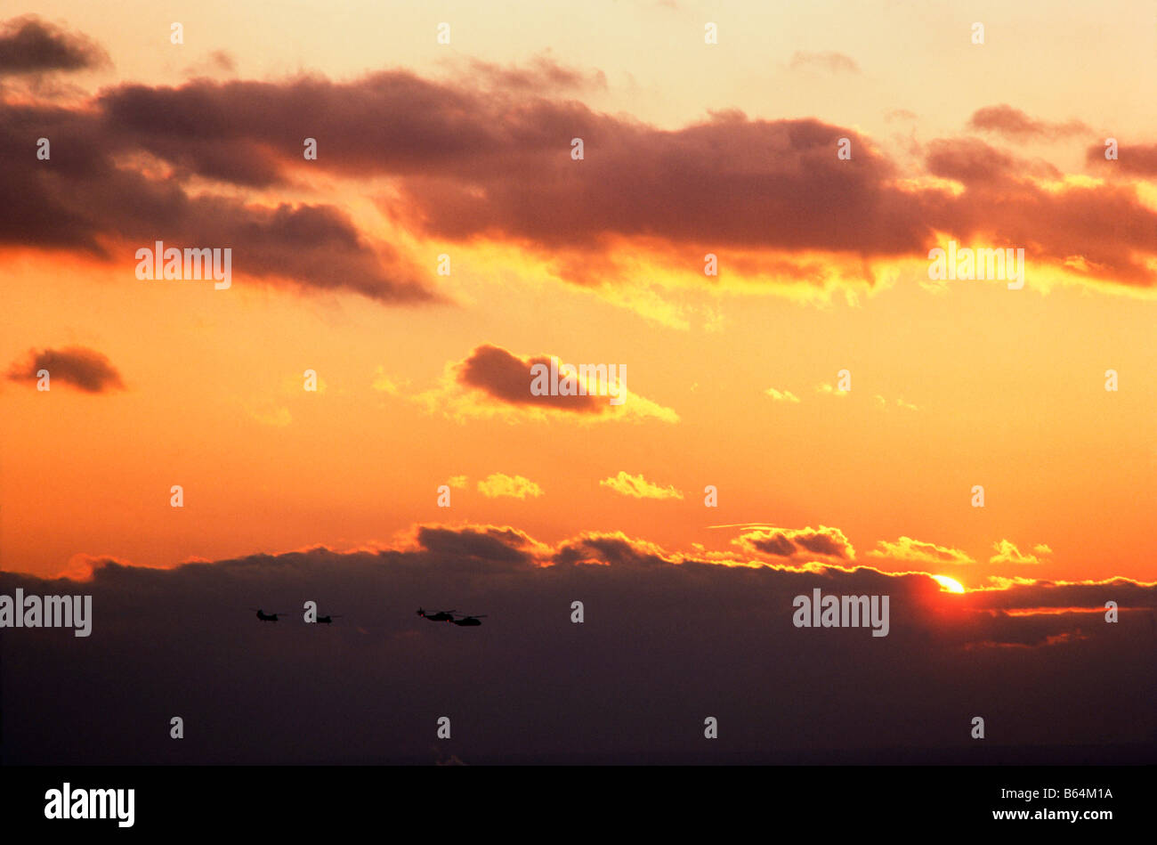 Severl military helicopters in flight at sunset - Stock Image