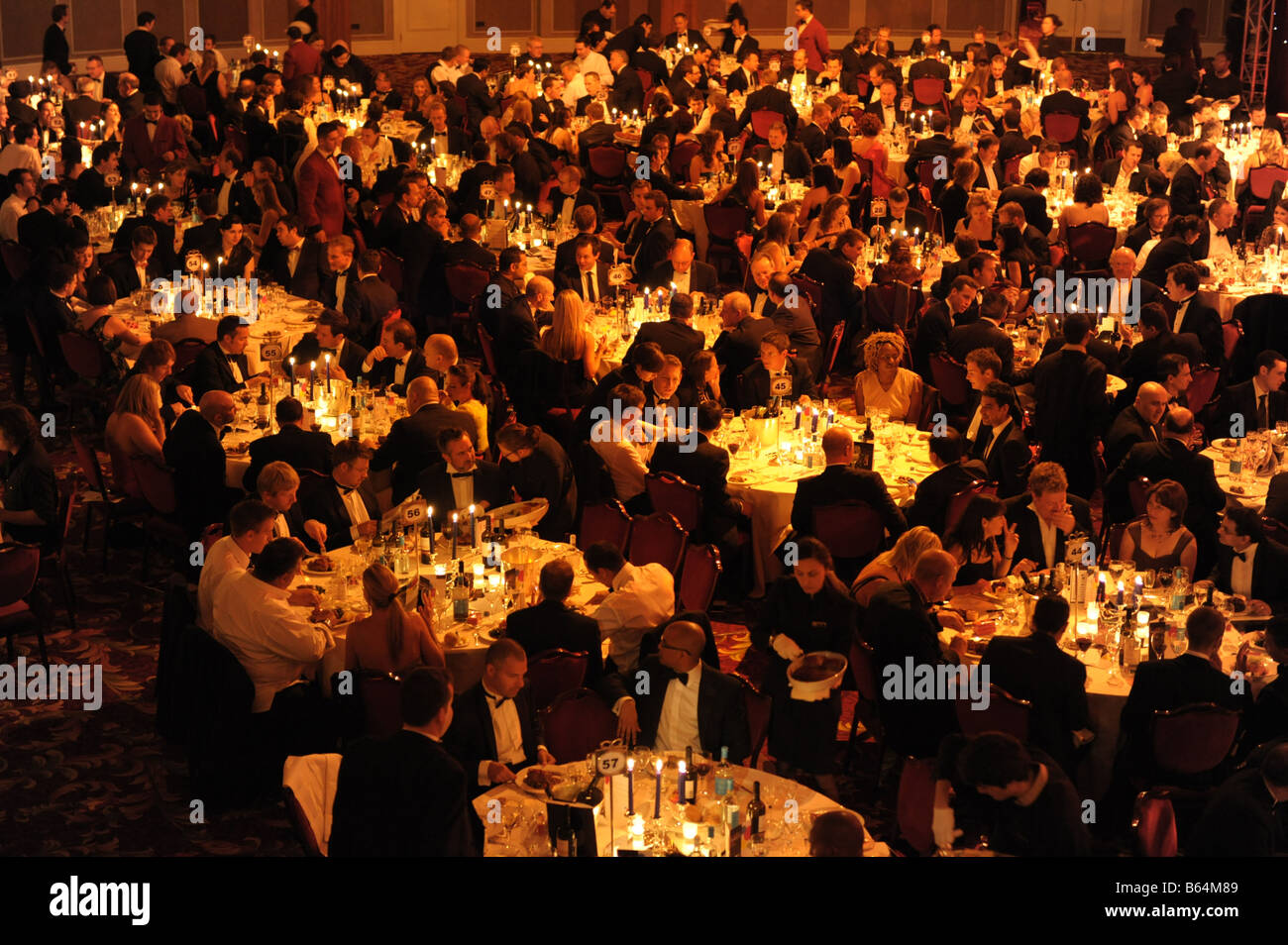 Large group of people seated at tables at evening business formal black tie event. Smart gala dinner, elevated view. Stock Photo