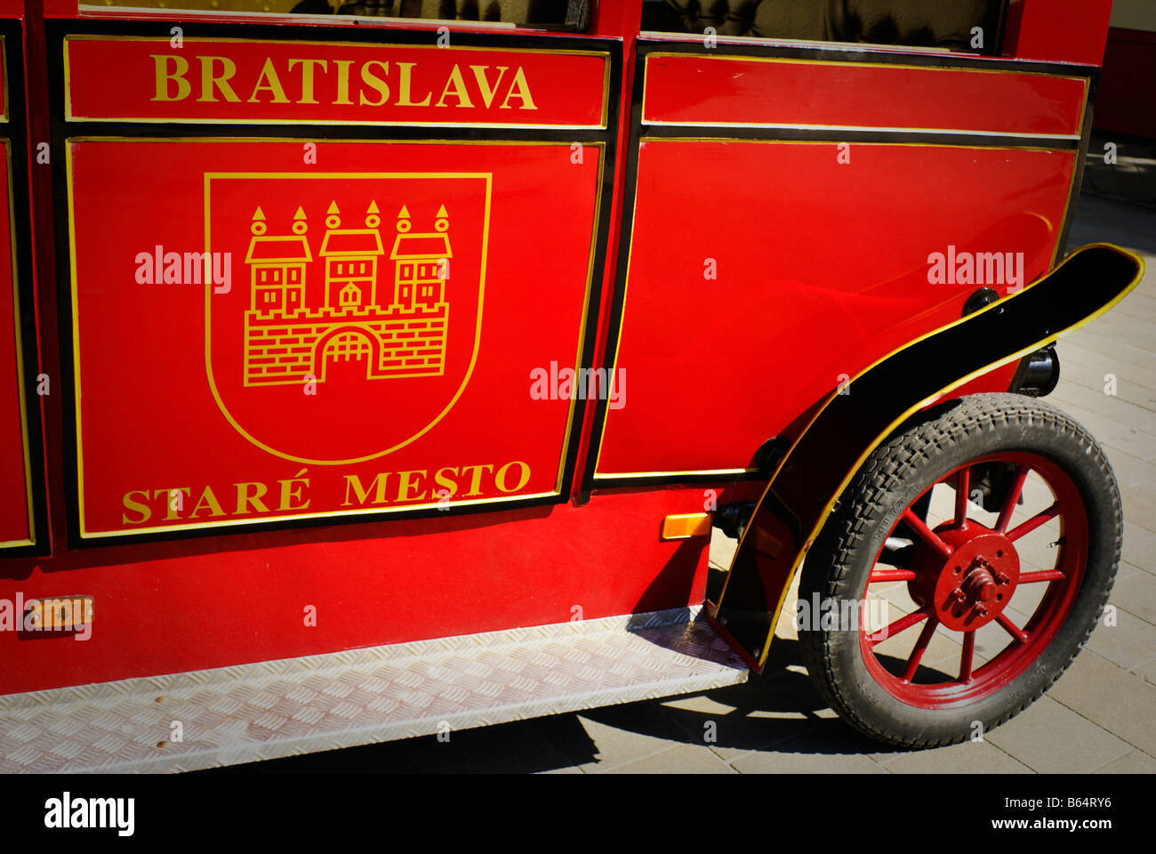 Red tourist sightseeing train in main central square in old town Bratislava. - Stock Image