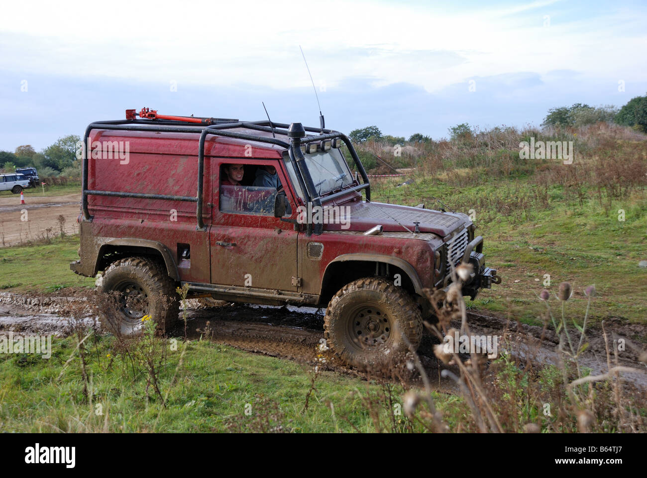 Mud splattered Land Rover Defender 90 kitted out for off road work with raised suspension anti roll cage winch lugged - Stock Image