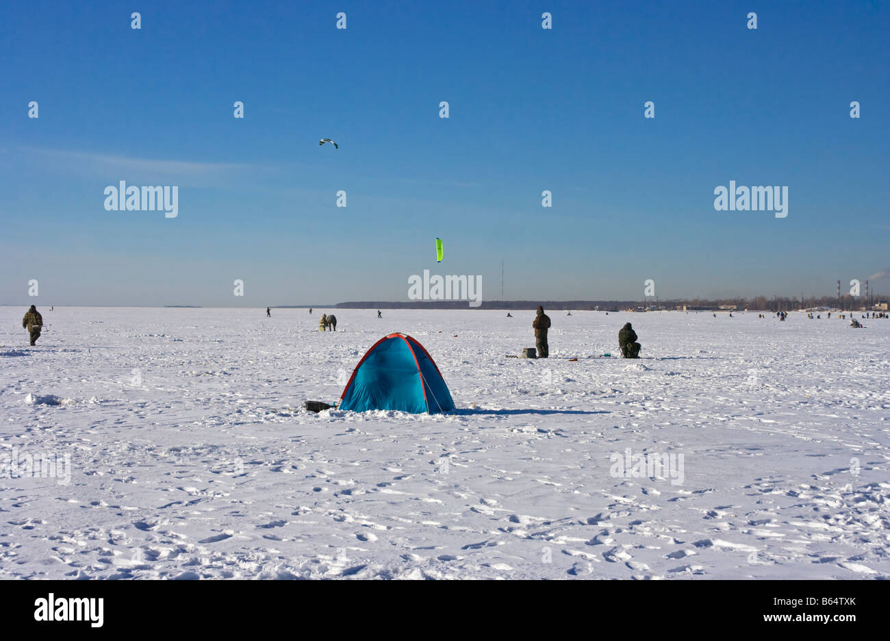 Sportsmen and fishers on ice of Gulf of Finland in sunny February day, St. Petersburg - Stock Image