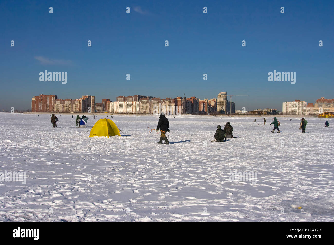 Fishers on ice of Gulf of Finland in sunny February day, St. Petersburg - Stock Image
