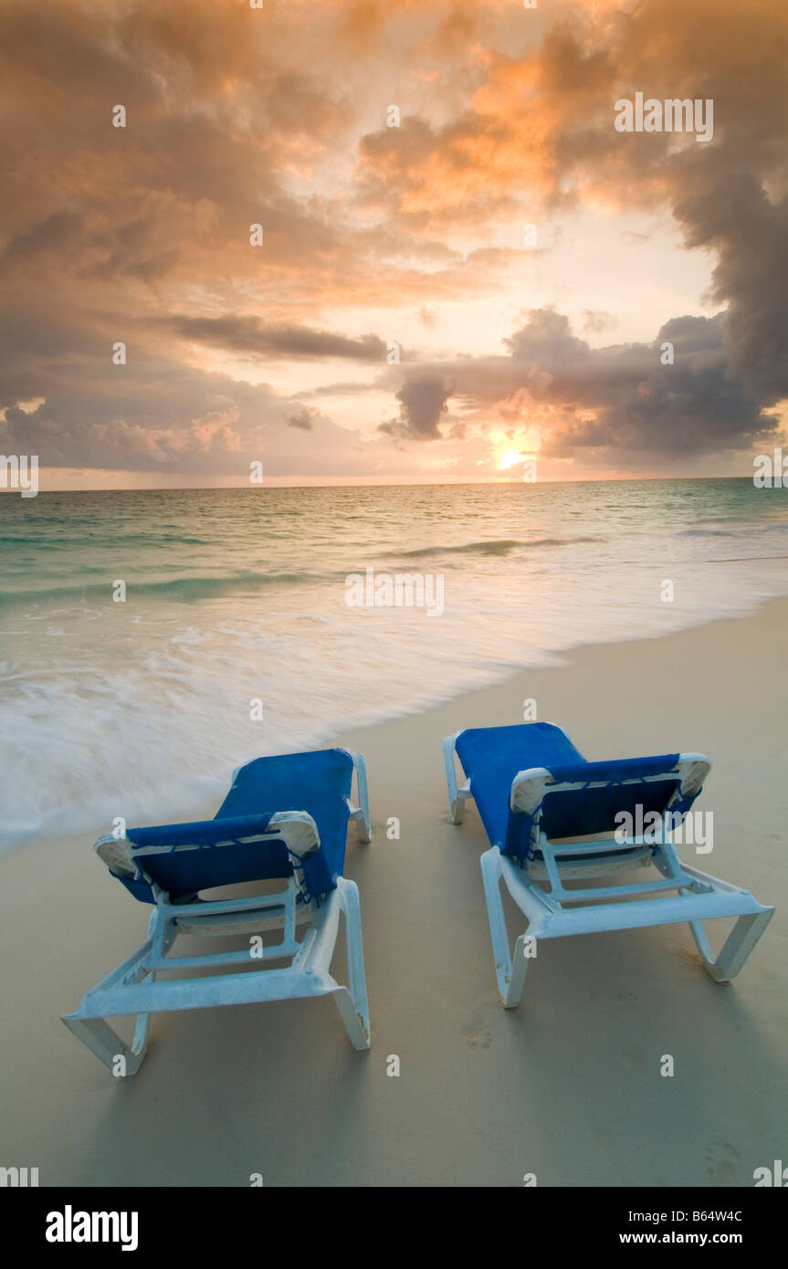 Caribbean Dominican Republic couple of lounge chairs on beach at sunrise in front of all inclusive resort - Stock Image