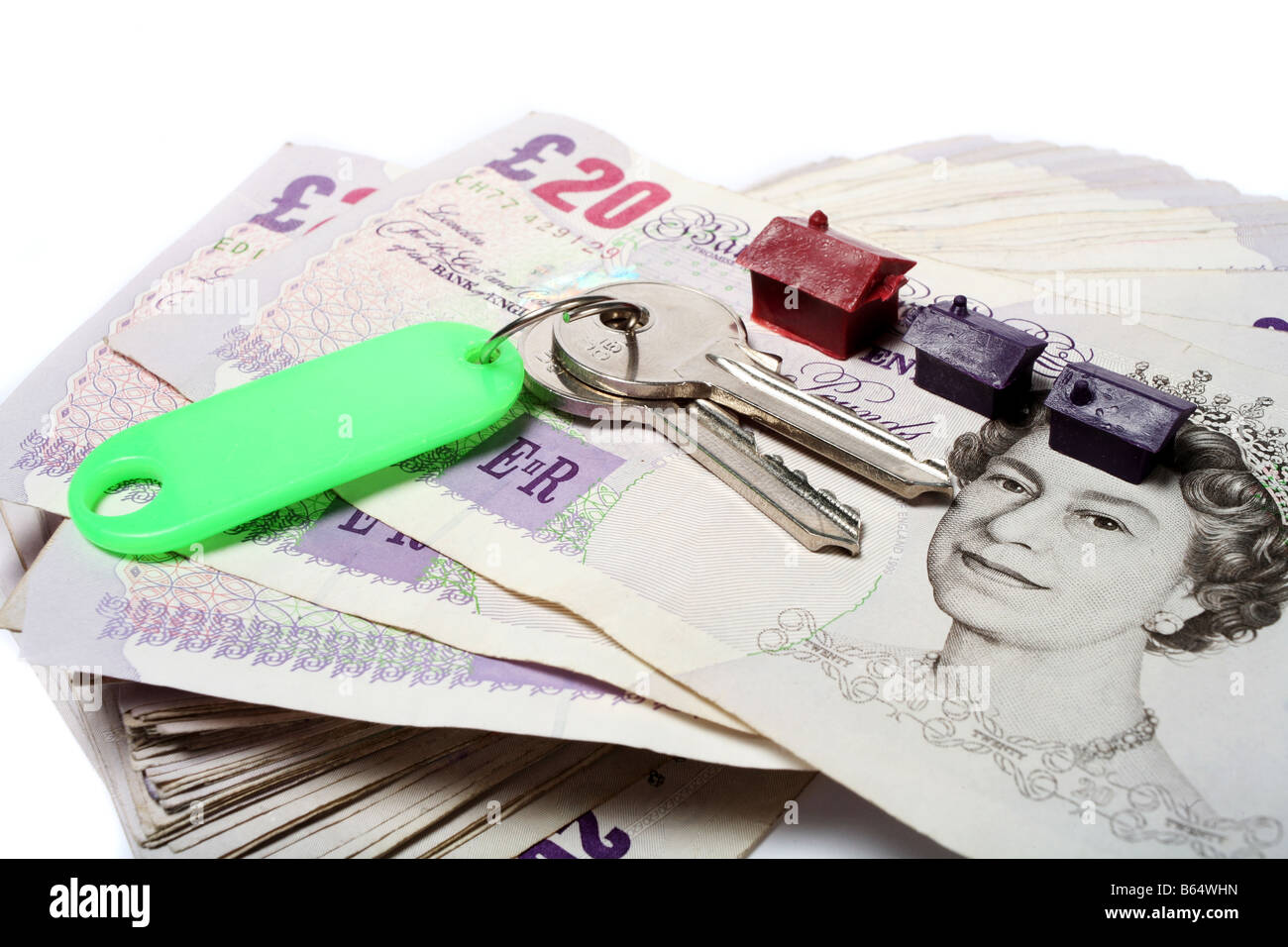 A set of house keys resting on a big pile of used 20 pound notes with some toy houses perhaps a rent or mortgage - Stock Image