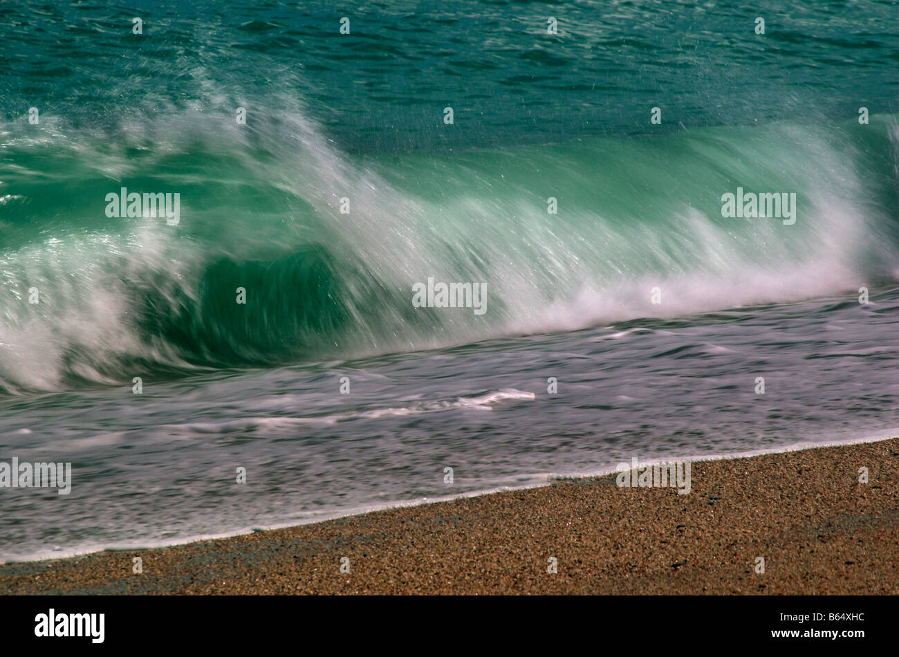 A wave breaking on a beach - Stock Image