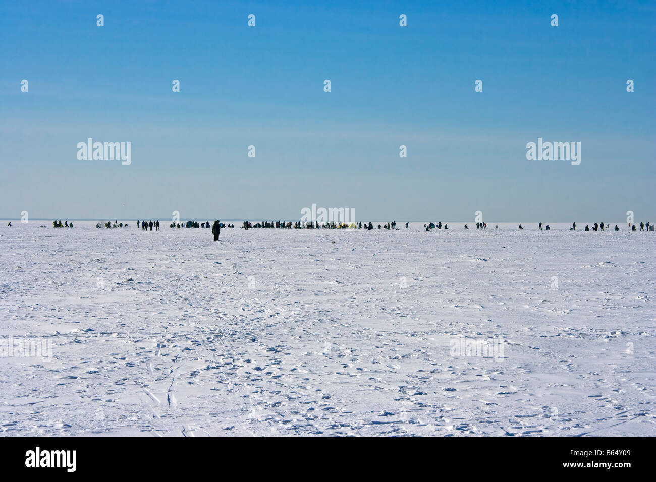 Fishers on ice of Gulf of Finland in sunny February day near St. Petersburg - Stock Image