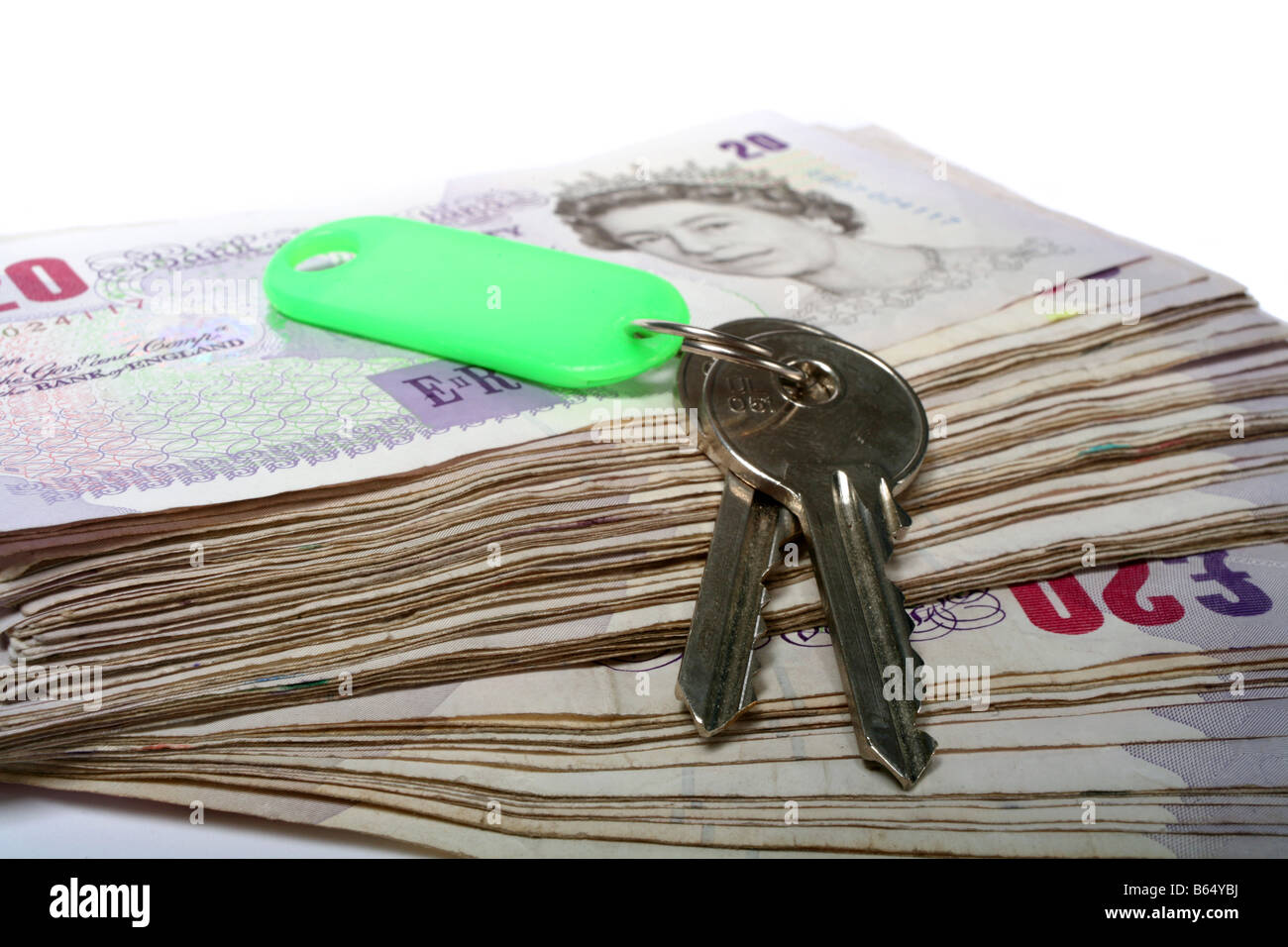 A set of house keys resting on a big pile of used 20 pound notes perhaps a rent or mortgage payment or the keys - Stock Image