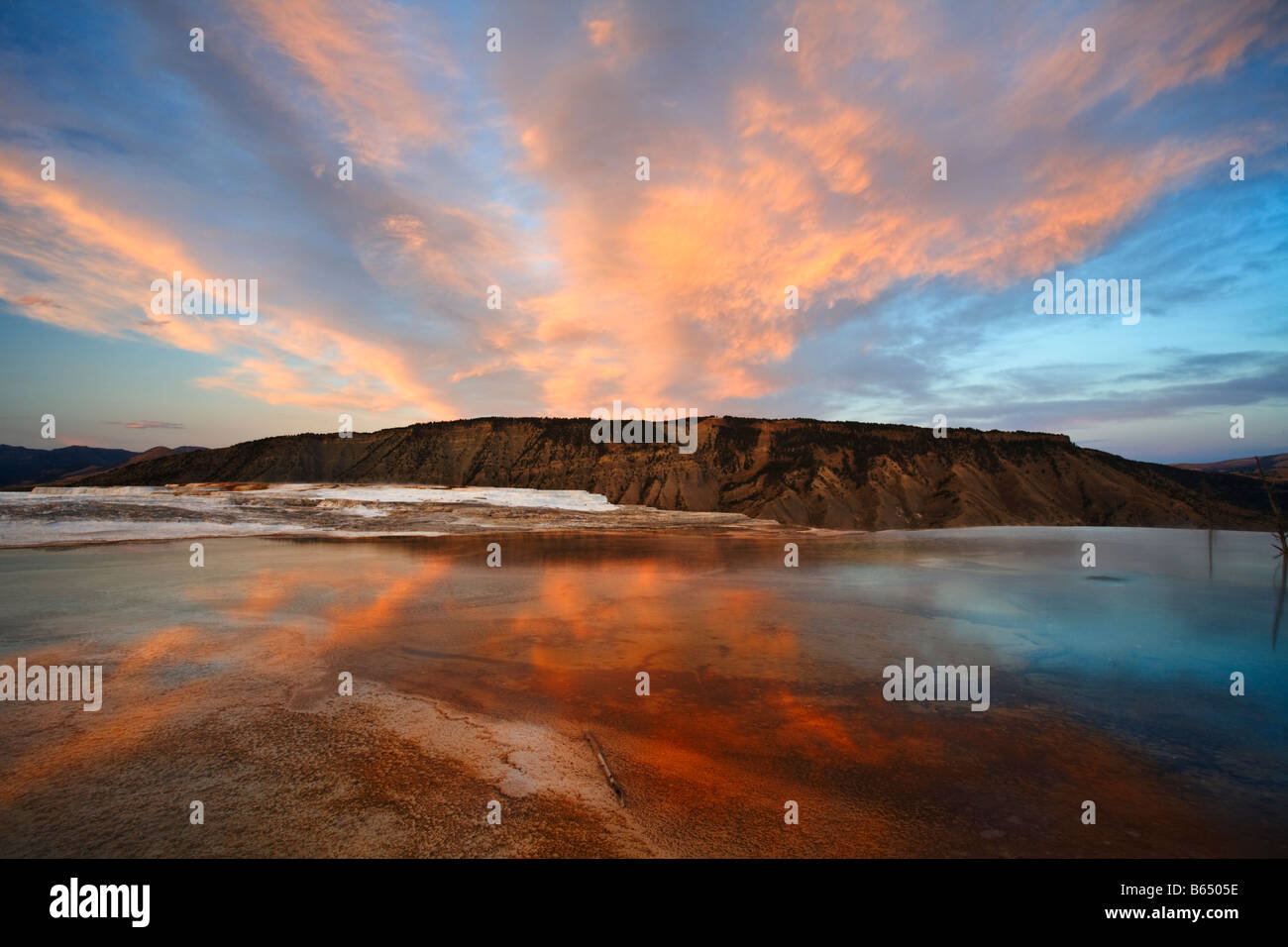 Yellowstone National Park WY: Colors of evening sky reflected on the pools and upper terrace of Mammoth Hot Springs - Stock Image