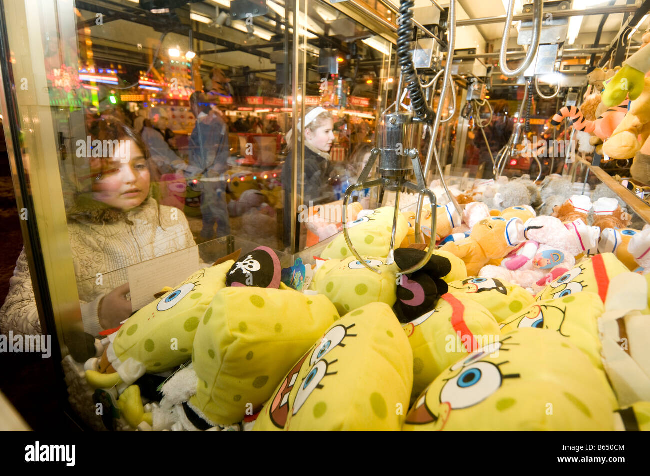 A young girl trying to win a soft toy prize on a fairground amusement arcade mechanical grab grabber game, UK - Stock Image