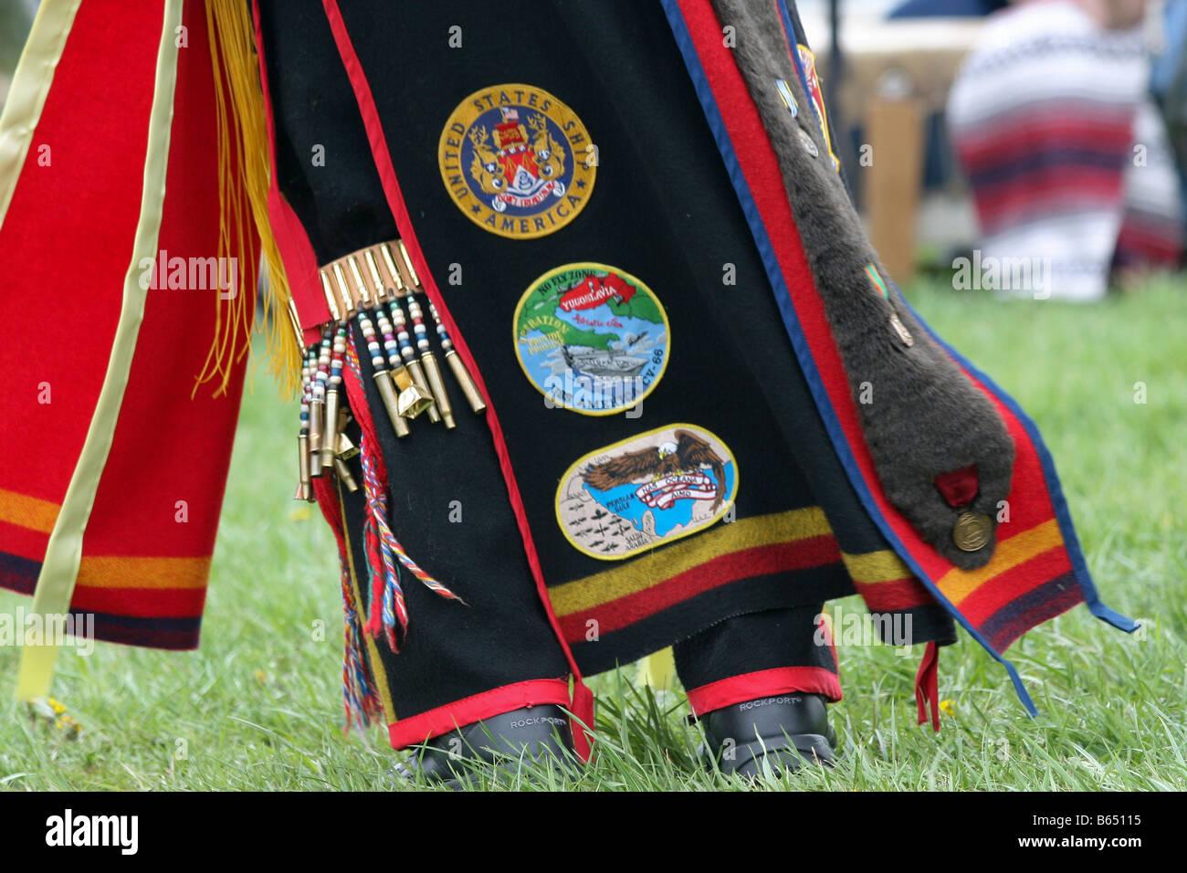 A Native American sports U.S. military badges sewn onto his traditional regalia. Stock Photo