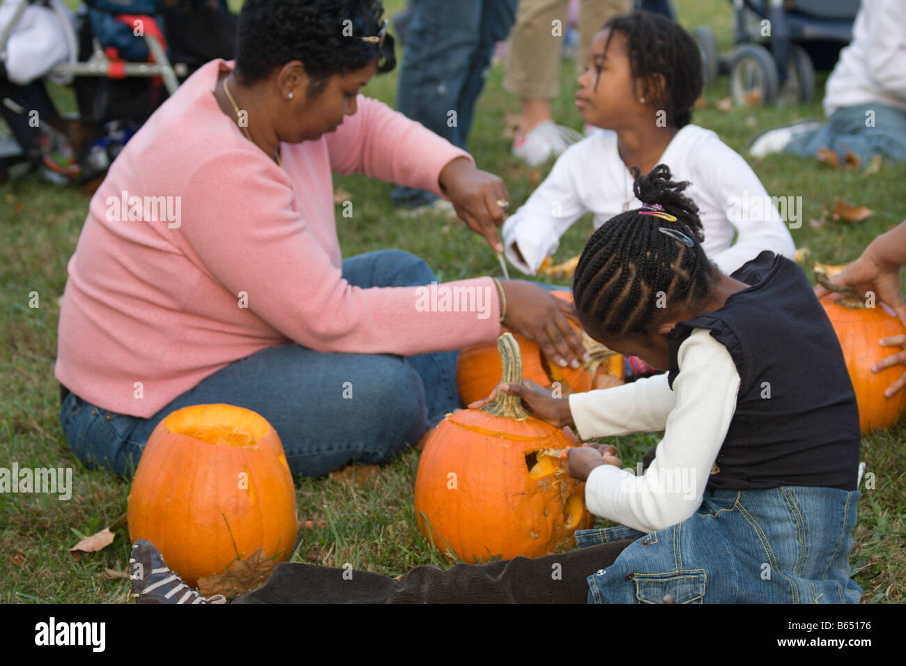 Mother and children carve pumpkins donated by Nalls Farm Market at the 2008 Shenandoah Valley Hot Air Balloon Festival - Stock Image