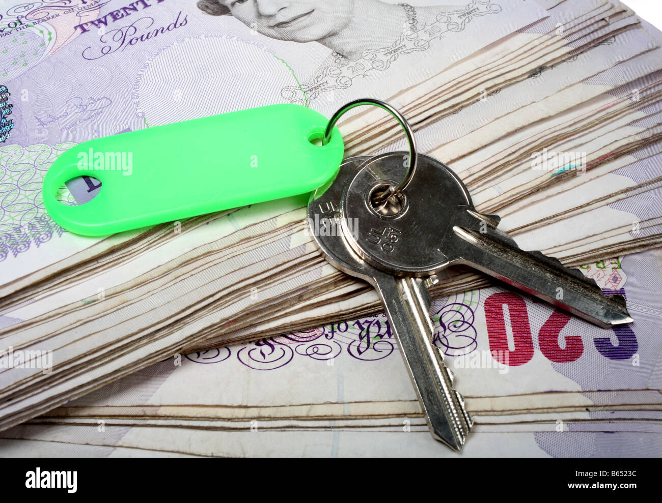 A set of house keys resting on a big pile of used 20 pound notes - Stock Image