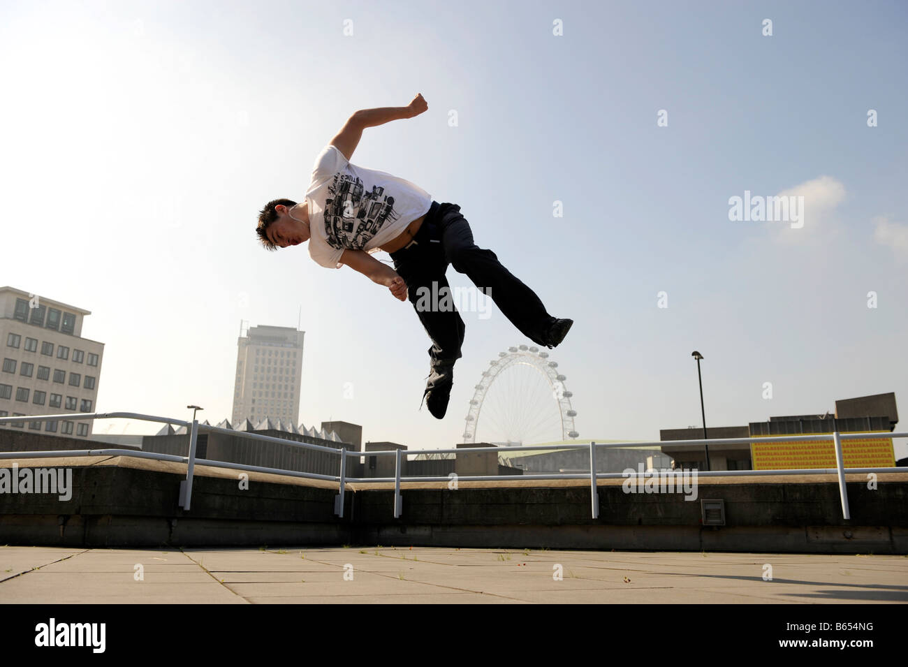 Danny Darwin demonstrating free running (parkour) techniques with the London Eue in the background - Stock Image
