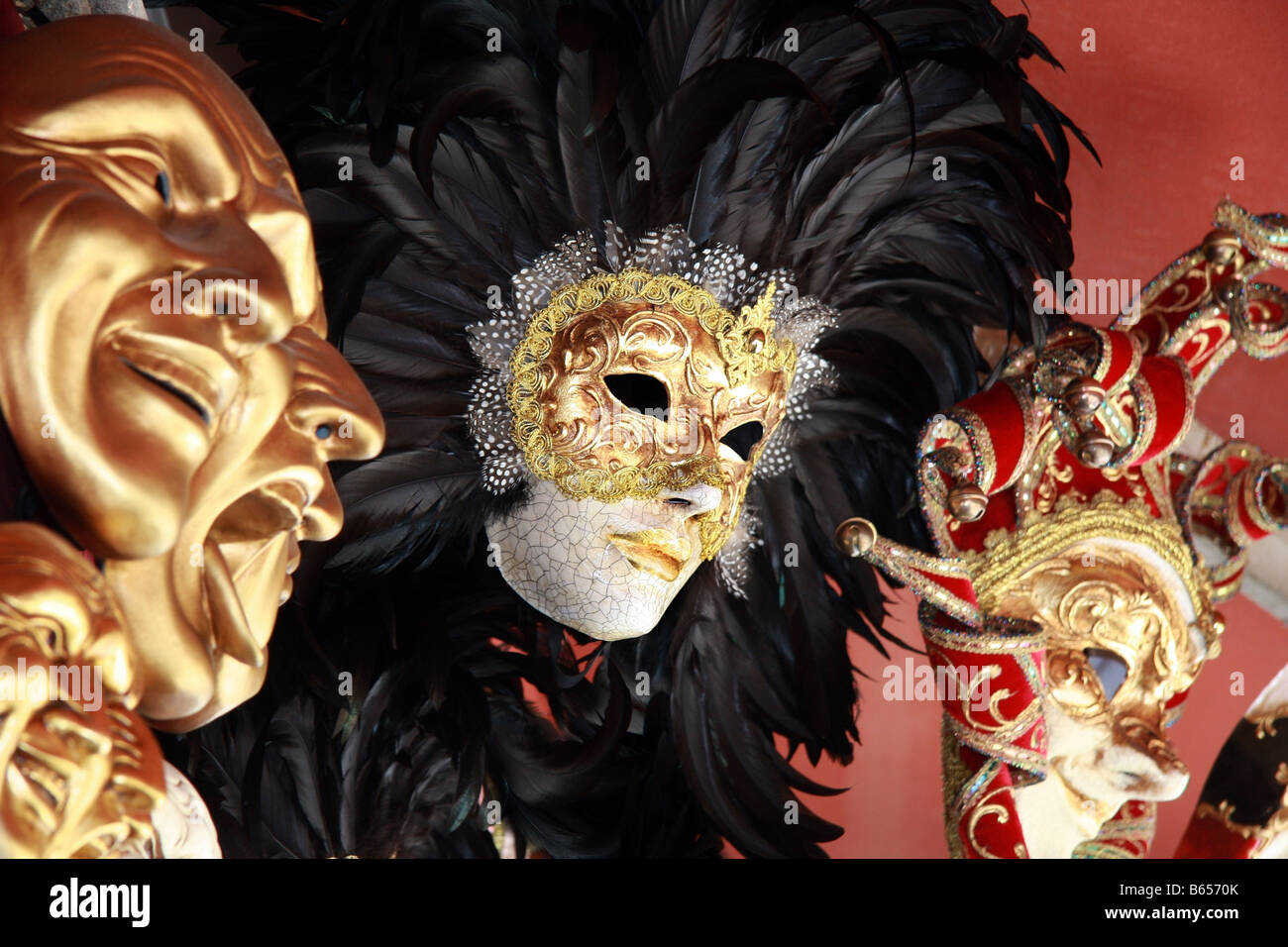 Venetian masks with black feathers on a red background - Stock Image