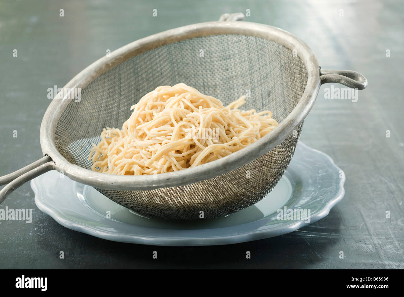 Spaghetti in metal colander resting on plate - Stock Image