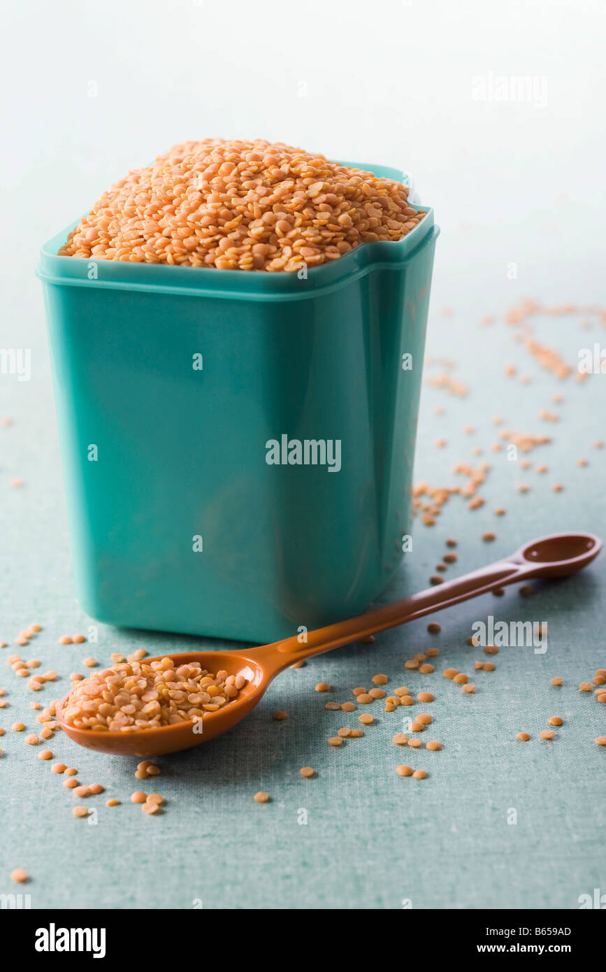 Red lentils in plastic canister, tablespoon of lentils nearby - Stock Image