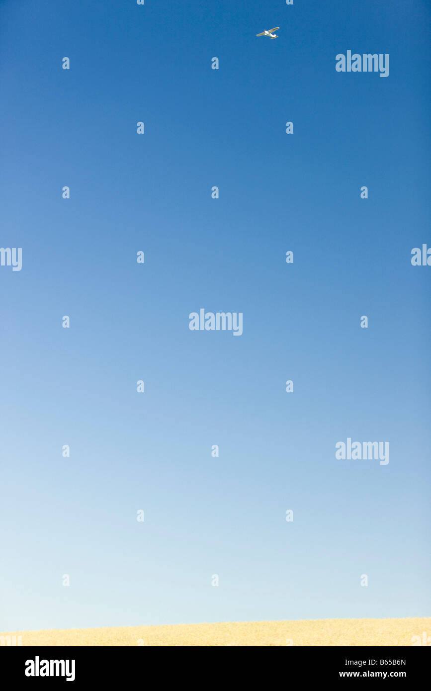 Clear blue sky, plane high in the distance - Stock Image