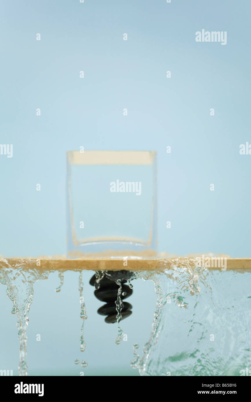 Pile of stones upside down, water flowing from inverted glass over ledge - Stock Image