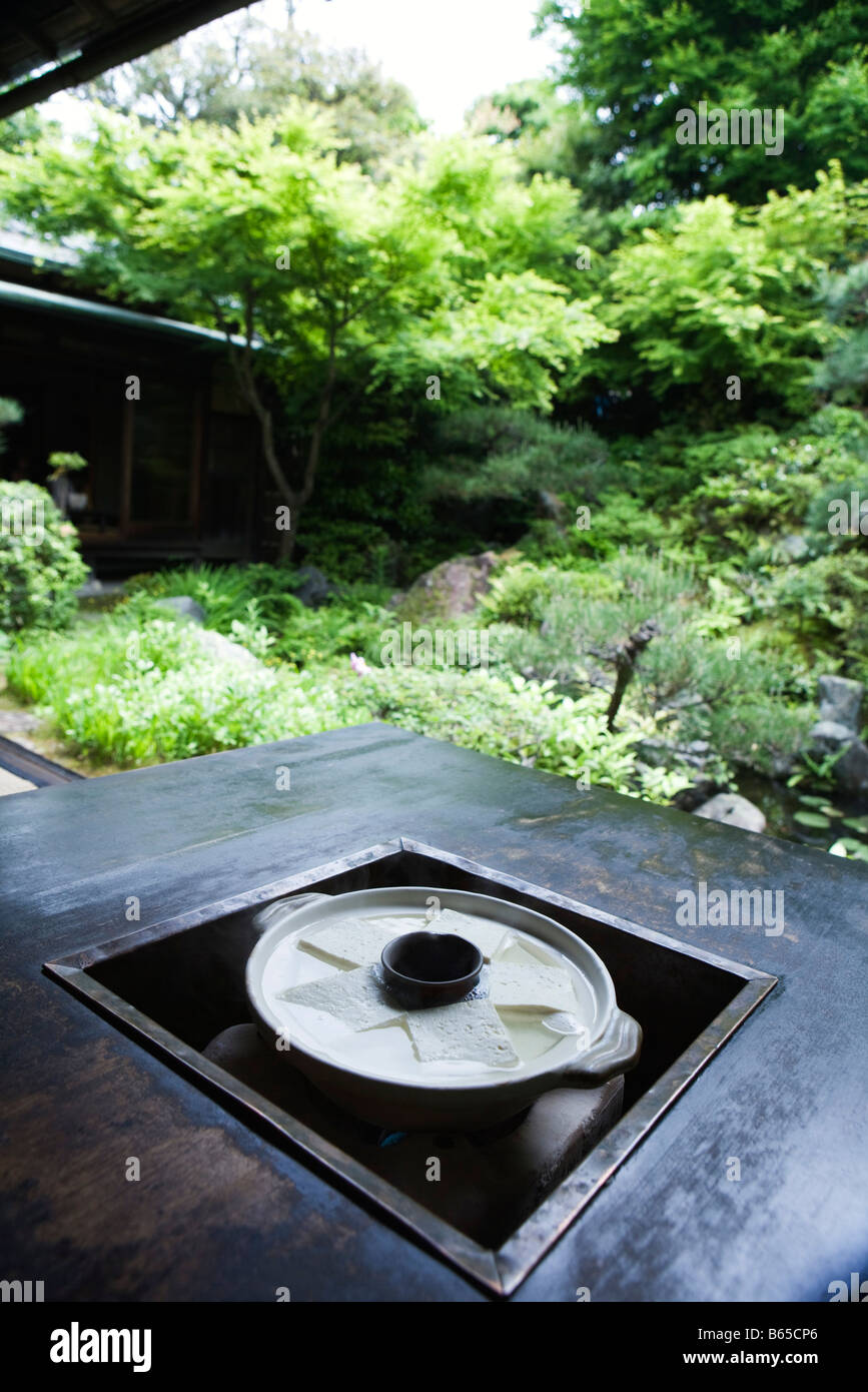 Yudofu cooking in pot on outdoor stove - Stock Image