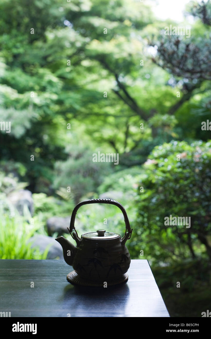 Teapot resting on table, Japanese scenery in background - Stock Image