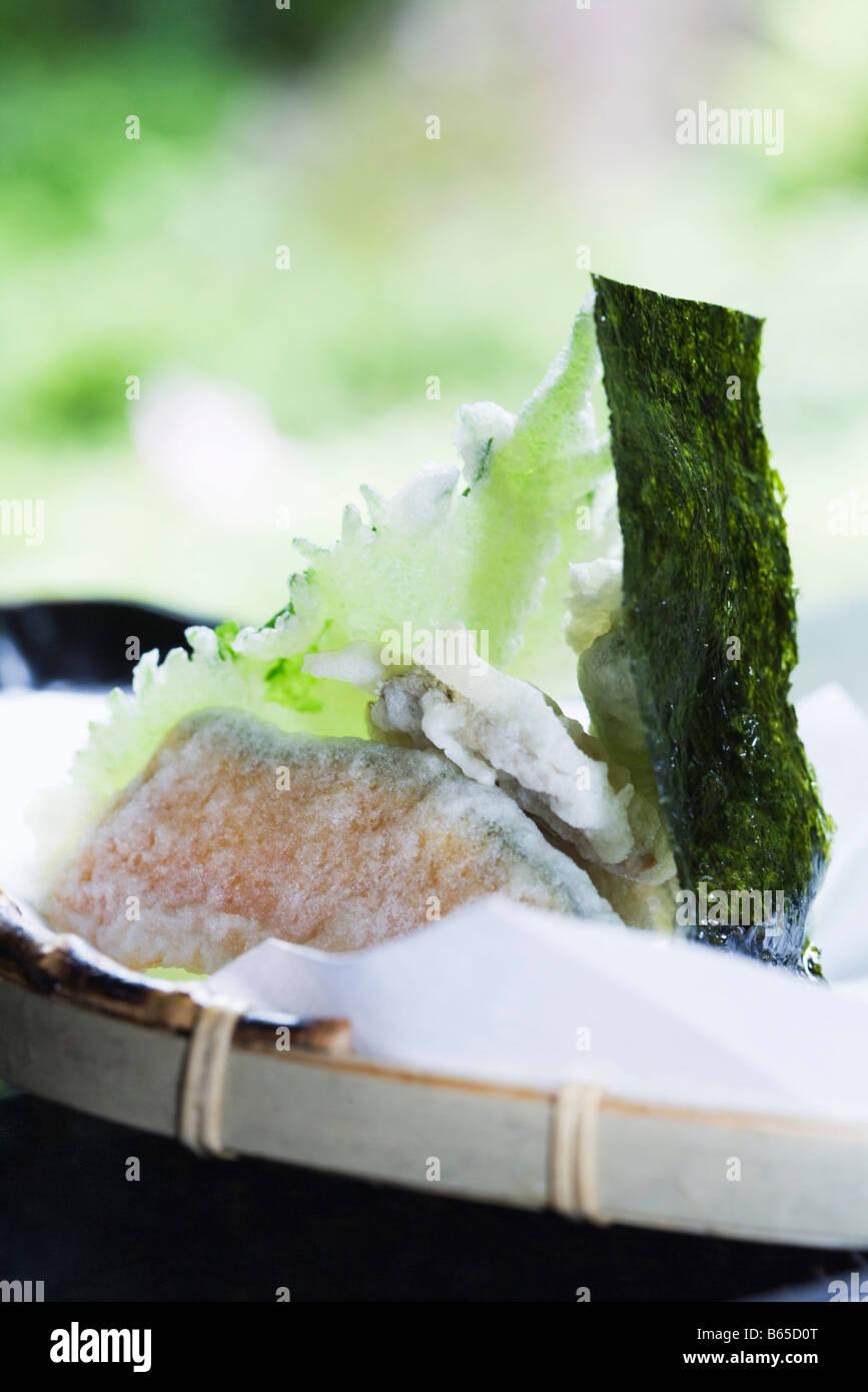 Winter squash and shiso tempura with piece of nori, close-up Stock Photo