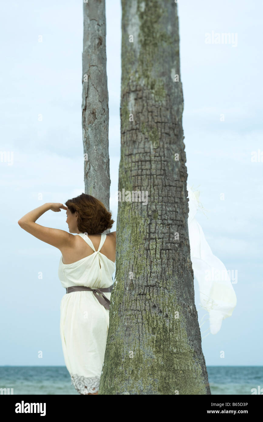 Woman standing amongst palm trees, looking at view of ocean, rear view - Stock Image