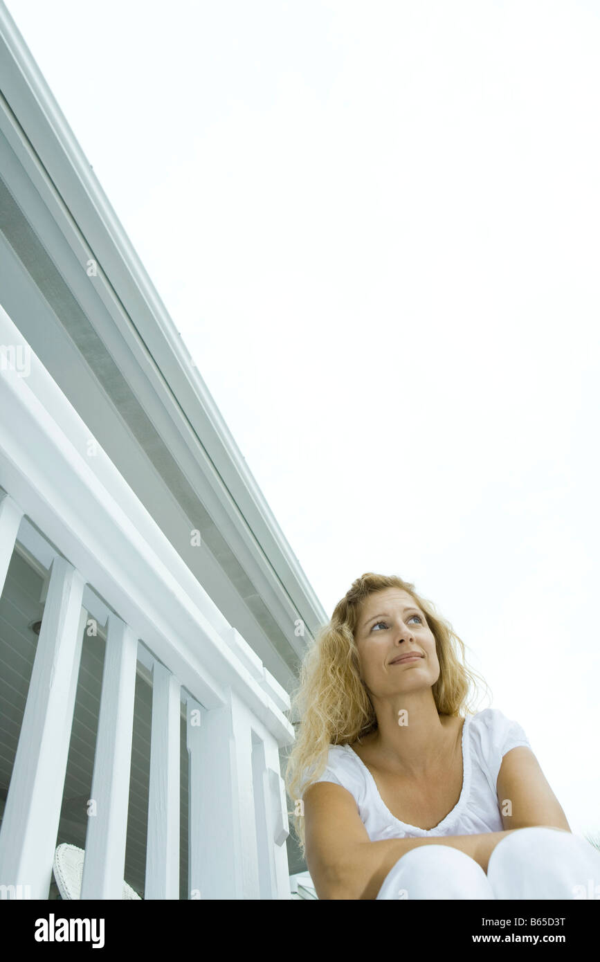 Woman sitting on porch, looking up, low angle view - Stock Image