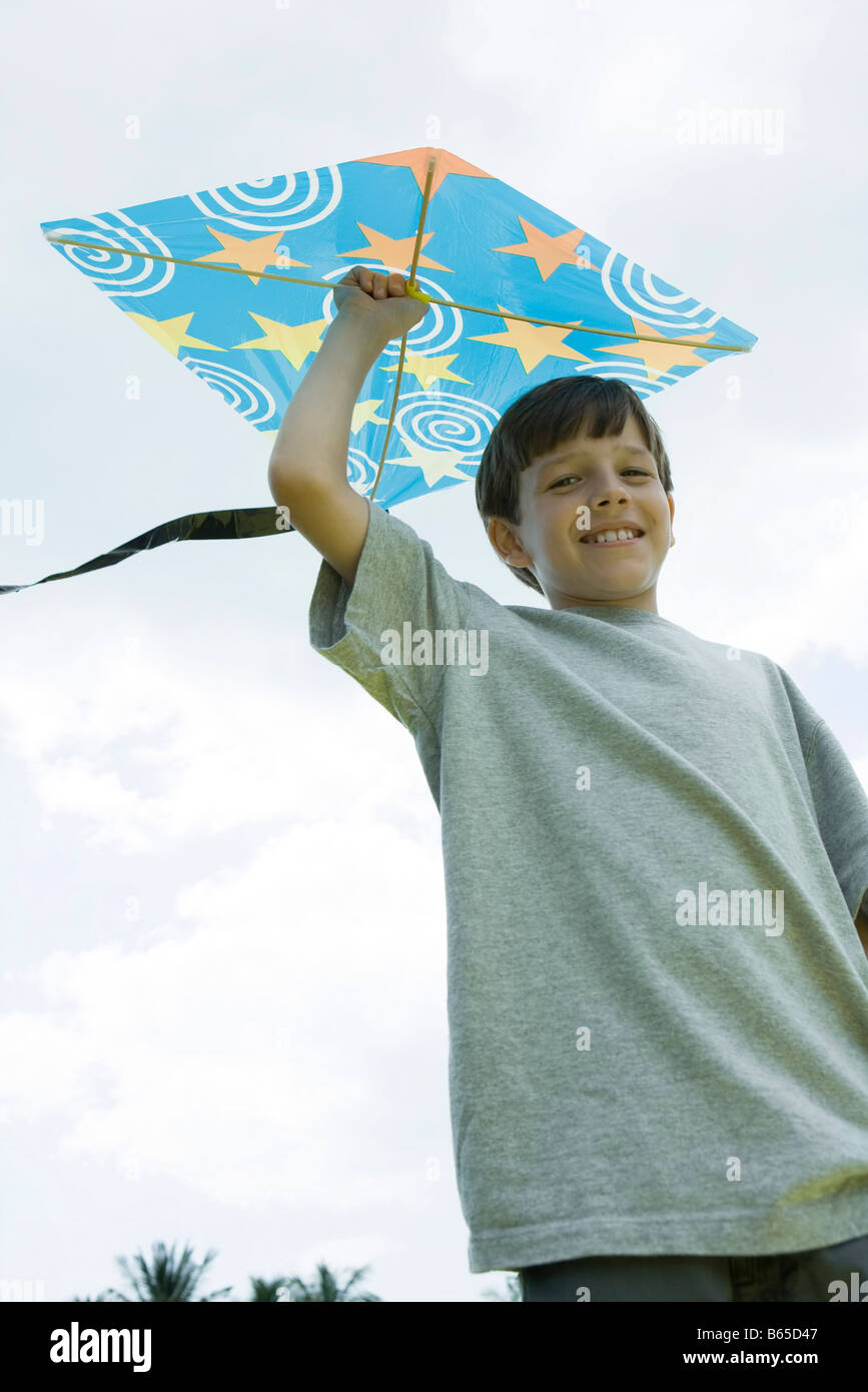 Boy holding kite above head, smiling at camera, low angle view - Stock Image