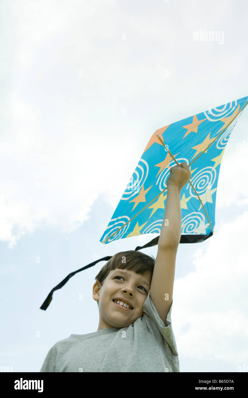 Boy holding kite above head, low angle view - Stock Image