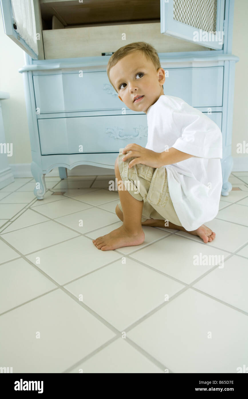 Boy crouching beside open armoire, looking over shoulder - Stock Image