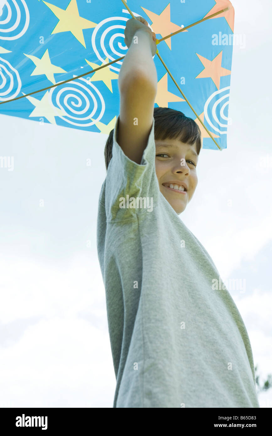 Boy holding kite above head, smiling, portrait - Stock Image