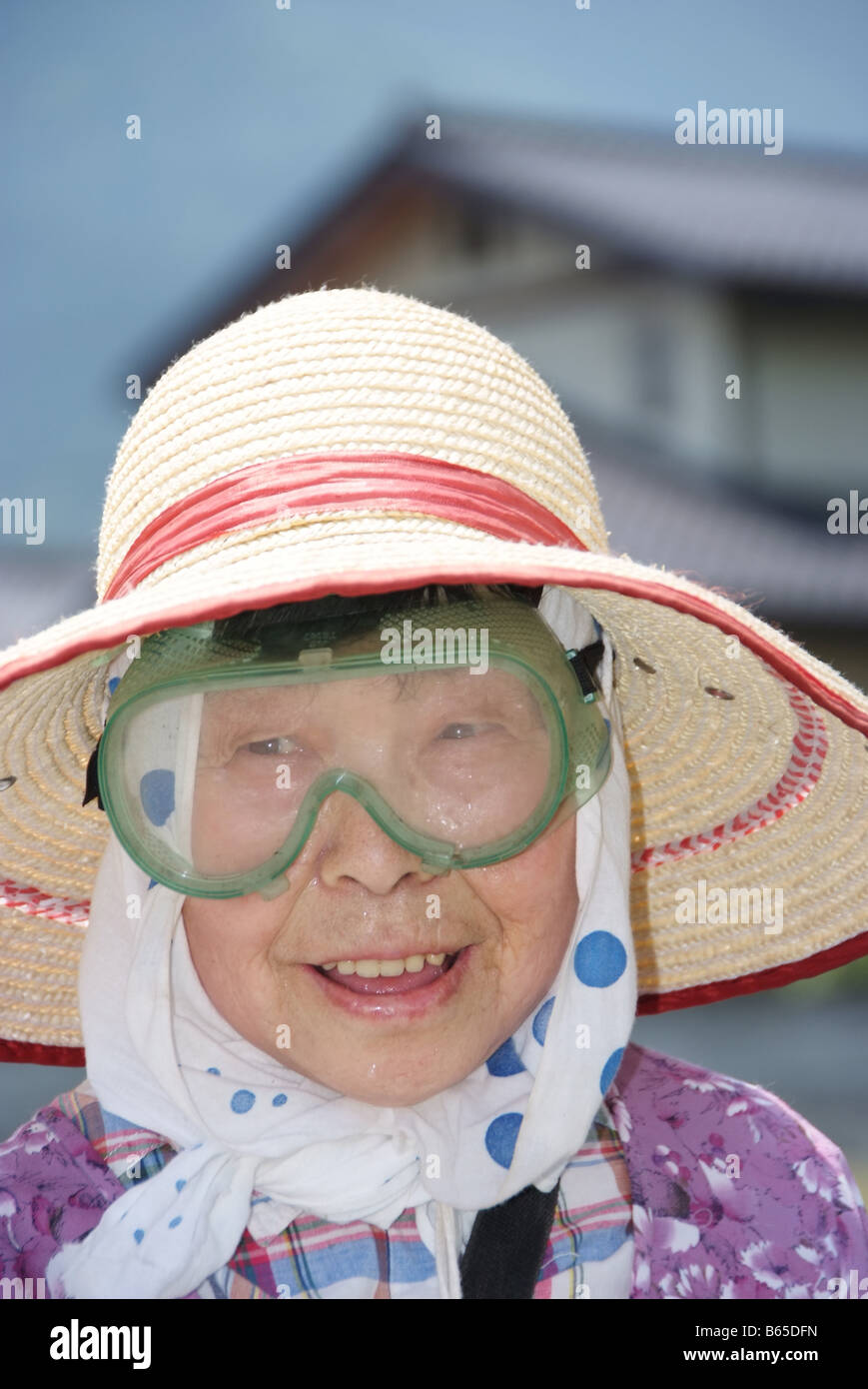Portrait of an old lady with goggles cutting grass Stock Photo